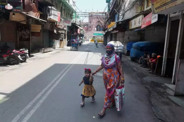 New Delhi: A woman walks with her kid during COVID-induced lockdown on a deserte...