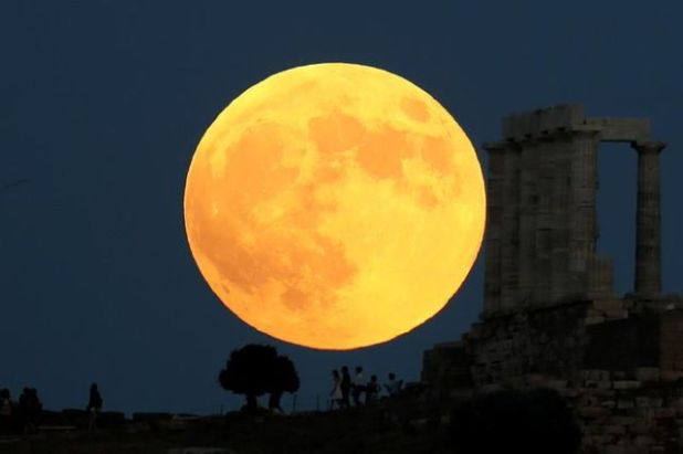 People watch a full moon rise behind the Temple of Poseidon before a lunar eclipse at Cape Sounion, near Athens, Greece.