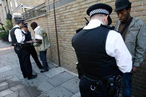 Des officiers de police fouillent deux hommes à Brixton, un quartier de Londres.