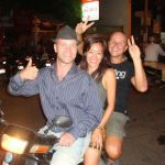 Ramon Stoppelenburg driving a moto with two passengers in Cambodia