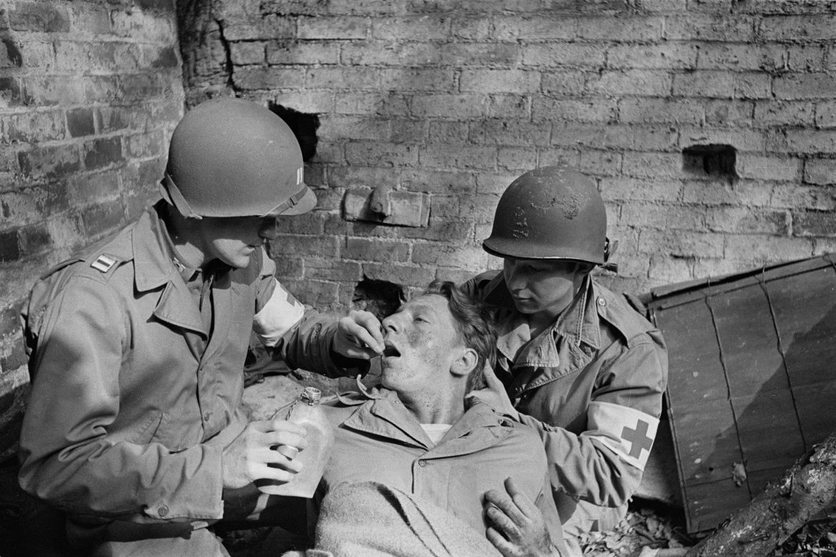 "An American soldier in WWII suffering from ""battle shock"" is given a sedative by a medic. ..."