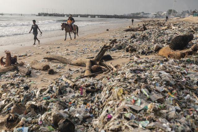"Turistas a cavalo na Praia de Kedonganan, Bali, 27 de janeiro de 2019. Todos os anos, durante a época de chuvas, de novembro a março, chegam às praias toneladas de lixo, dando à temporada o apelido de ""época do lixo""."
