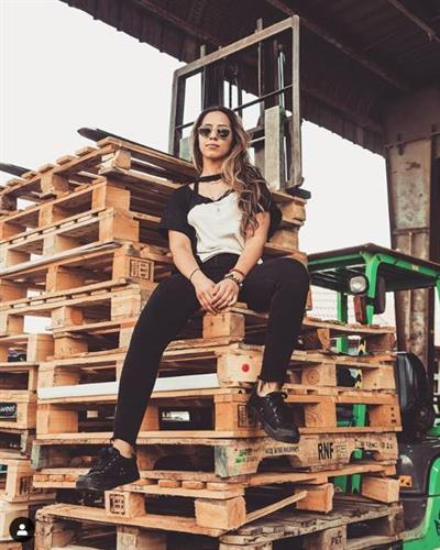 Award winning chef and social media influencer Tala Bashmi sitting on a stack of shipping pallets