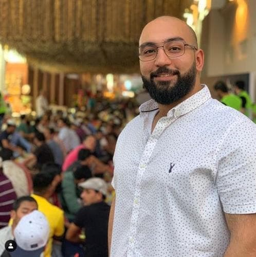 Bahraini influencer and restaurant reviewer Mohammed Wedo smiling with restaurant patrons in the background