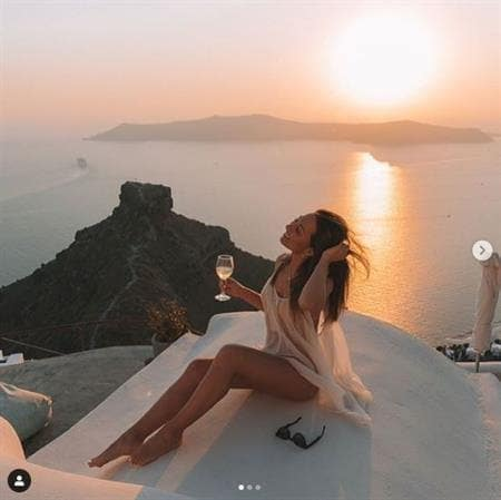 Australian travel influencer Laura McWhinnie enjoying a glass of wine and a gorgeous sunset in Santorini
