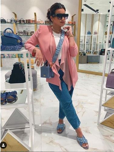Fashion and beauty influencer Amal Al Aradi posing in a boutique in denim, sandals, and a pink cardigan