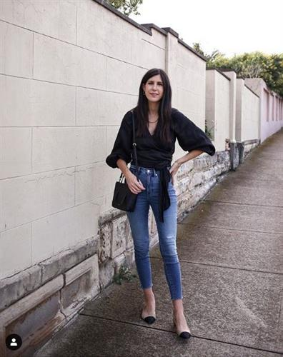 Aussie fashion influencer Jamie-Lee dressed in a black wrap shirt and cropped jeans styled with a black handbag and flats