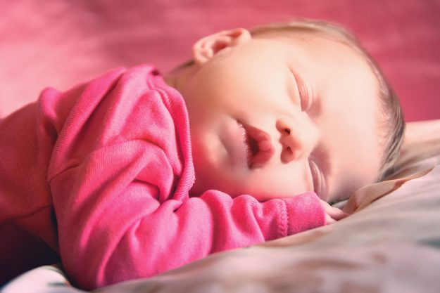 sleeping newborn baby girl in pink