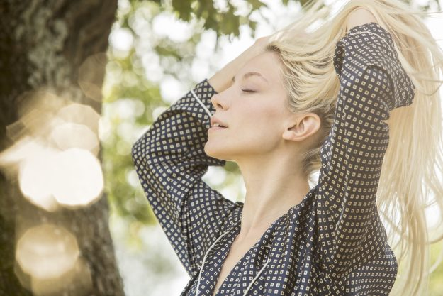 Blond woman with eyes closed and hands in her hair in the morning