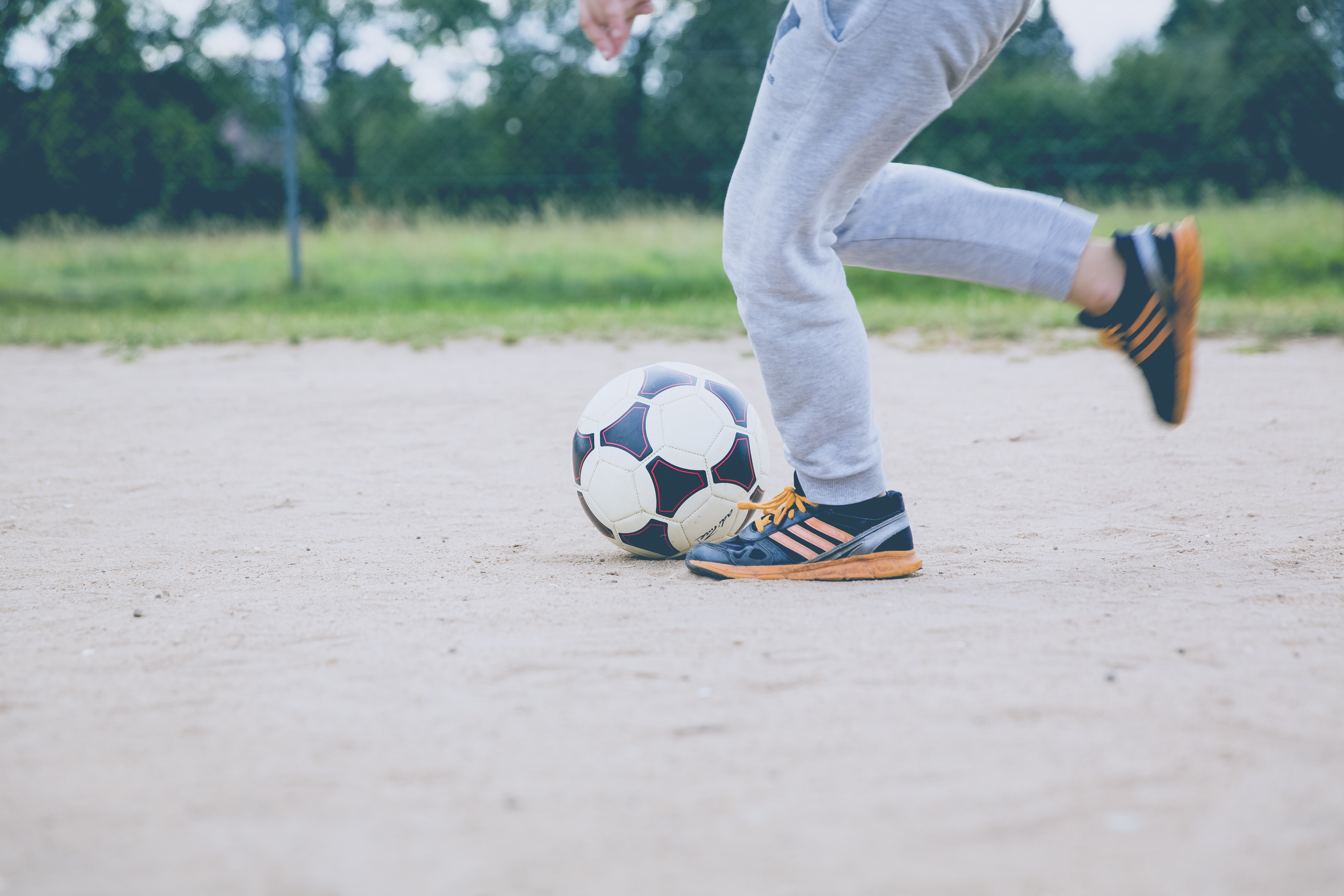 Person Kicking Soccer Ball on Gray Sand  Free Stock Photo