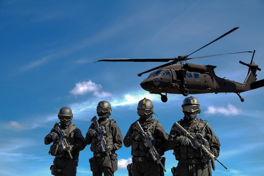 SWAT officers stand under a hovering SWAT helicopter.