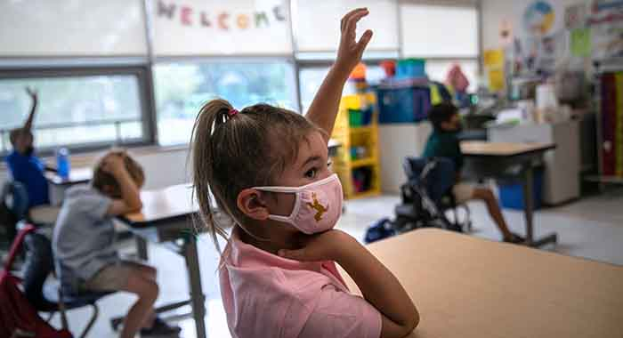 A kindergarten student raises her hand during her first day of school in Connecticut.