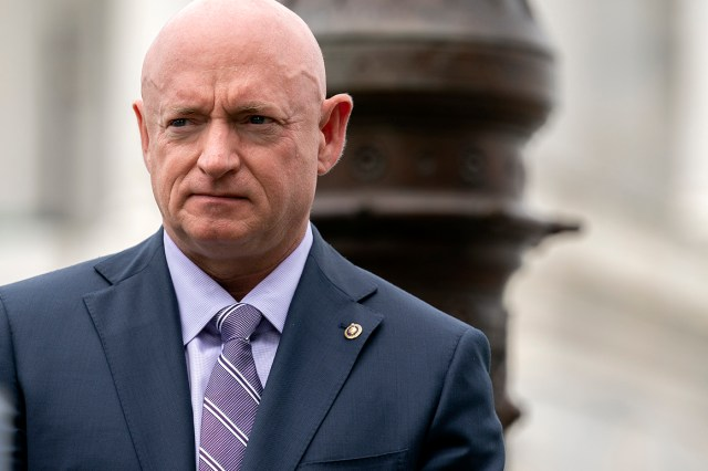 Sen. Mark Kelly listens during a news conference.