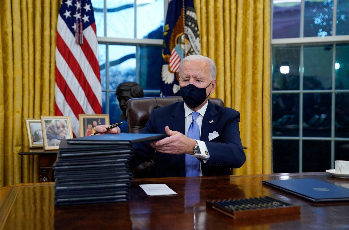 In this Jan. 20, 2021, file photo, President Joe Biden signs his first executive orders in the Oval Office of the White House in Washington. Thousands of people are waiting to claim asylum and more come each day, falsely believing they will be able to enter the U.S. now that former President Donald Trump is out of office. Biden has made significant changes to his predecessor's hardline immigration policies, but he hasn't lifted some major restrictions to people seeking asylum.