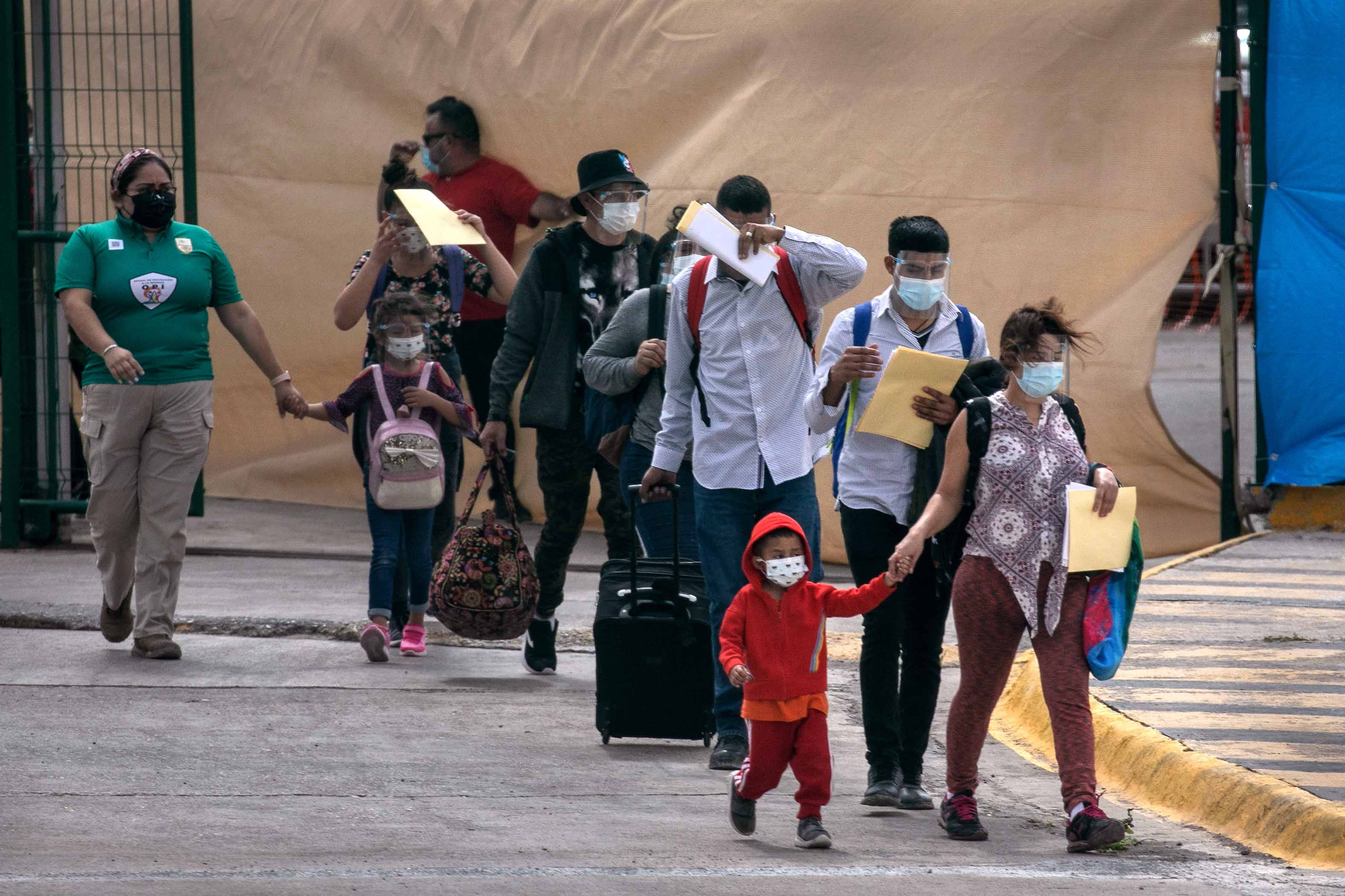 Asylum seekers walk to the U.S.-Mexico border as a group of at least 25 immigrants were allowed to travel from a migrant camp in Mexico into the United States.