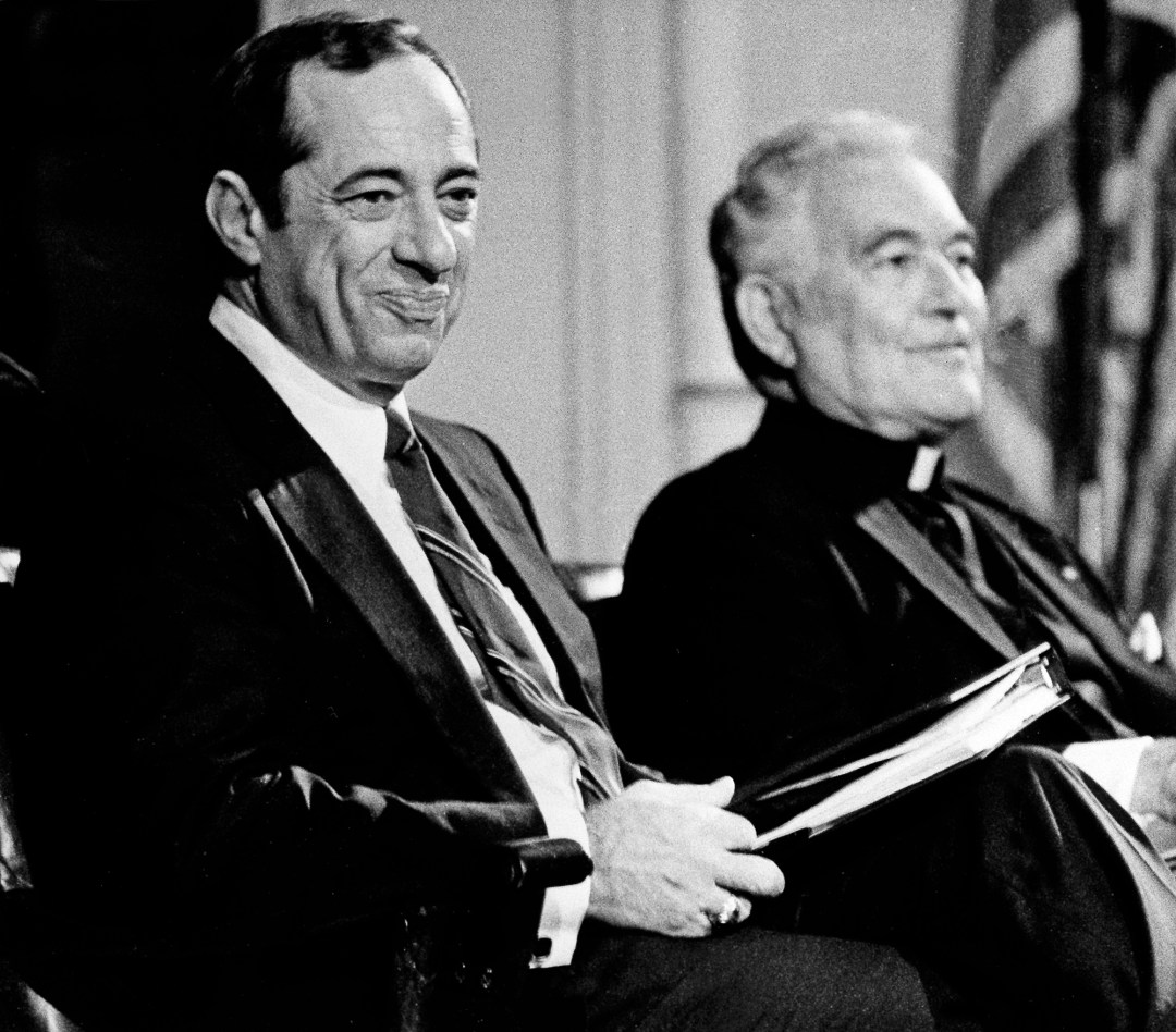 Prior to his lecture to his students at the Notre Dame campus in South Bend, Ind., New York Governor Mario Cuomo, left, smiles at comments made in his introduction, Sept. 13, 1984. Seated with Cuomo is University of Notre Dame President Rev. Theodore Hesburgh.