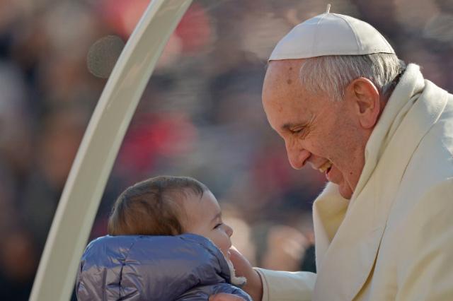 """Fruto del matrimonio.  Papa Francis sostiene a un bebé, fruto de un sacramento que él dice que no es """"fuera de moda"""".  Archivo de fotos Vincenzo Pinto / AFP"""
