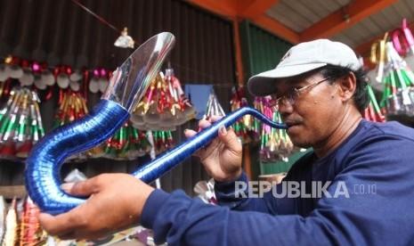 Pedagang mengecek suara terompet kertas yang sudah jadi di Kawasan Glodok, Jakarta, Rabu (27/12).
