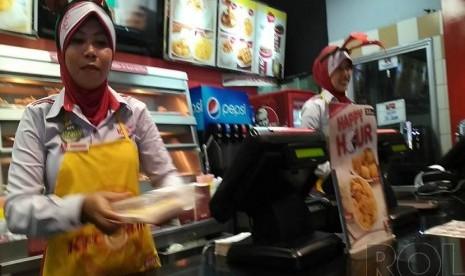 Pekerja sebuah restoran cepat saji di Banten, Ahad (7/12), mengenakan atribut Natal berupa tanduk rusa sebagai bagian seragamnya.