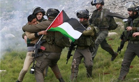 Pasukan keamanan Israel menahan seorang aktivis Palestina yang menentang pembangunan pemukiman Yahudi di Tepi Barat, Burin, Palestina, Sabtu (2/2).
