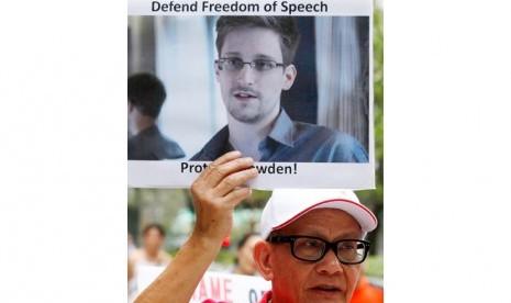 Seorang pengunjuk rasa memegang poster foto Edward Snowden, mantan karyawan CIA yang membocorkan informasi rahasia tentang program pengintaian AS, di luar gedung Konsulat Jenderal AS di Hong Kong, Kamis (13/6).    (AP/Kin Cheung)