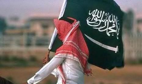 Seorang warga membawa bendera Arab Saudi (Ilustrasi)