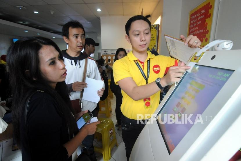 Petugas mengambilkan nomor antrian untuk warga yang akan melakukan registrasi ulang kartu SIM prabayar di Galeri Indosat, Kota Bogor, Jawa Barat, Rabu (28/2).