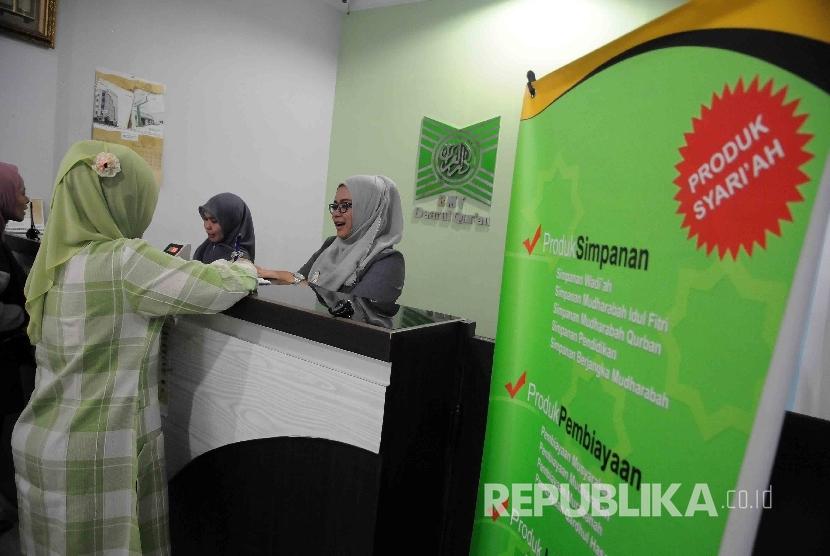 Karyawati melayani nasabah di koprasi simpan pinjam syariah baitul maal wa tamwil (BMT) Daarul Qur'an, Pal Batu, Jakarta, Senin (11/1).
