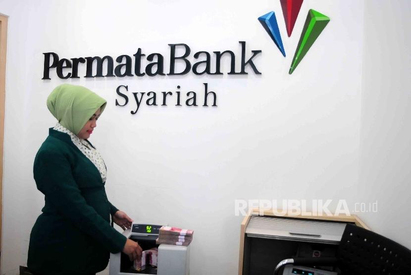 Karyawati menghitung uang di Banking Hall Bank Permata Syariah, Jakarta, Senin (9/5). (Republika/Agung Supriyanto)