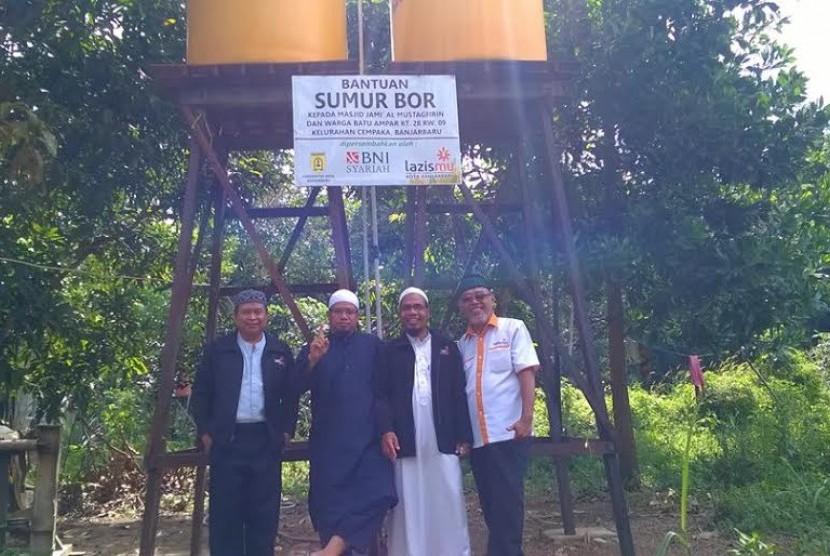 Lazismu menyerahkan bantuan sumur bor kepada masjid terpencil di Kalimantan.