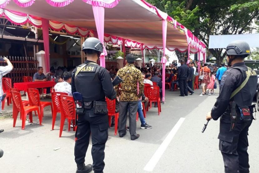 Personel Brimob mengamankan ibadah di Gereja BNKP Kota Padang, Sumatra Barat, Ahad (13/5). Menkumham Yasonna Laoly akan meresmikan pembangunan gereja tersebut.