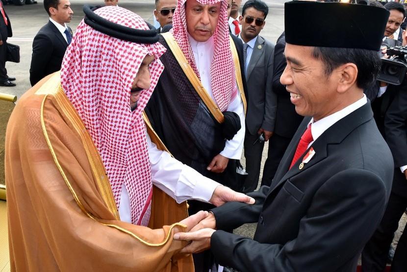 Presiden Joko Widodo menyambut Raja Arab Saudi Salman bin Abdulaziz Al-Saud (kiri) saat tiba di Bandara Halim Perdanakusuma, Jakarta, Rabu (1/3).