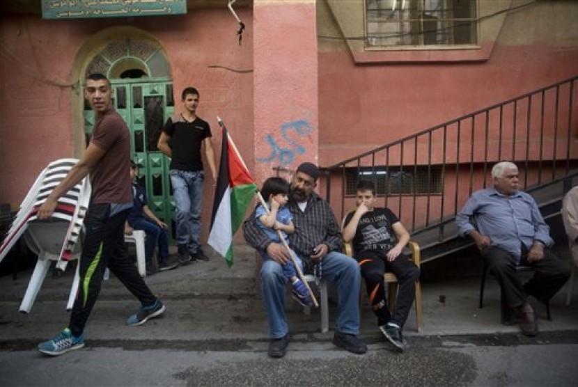 Seorang bocah laki-laki Palestina memegang bendera Palestina sambil duduk di pangkuan ayahnya di luar rumah keluarga ohammed Ali (19 tahun) di kamp pengungsi Shuafat di Yerusalem. Ali tewas setelah ia menusuk polisi Israel pada 10 Oktober dekat Gerbang Kot