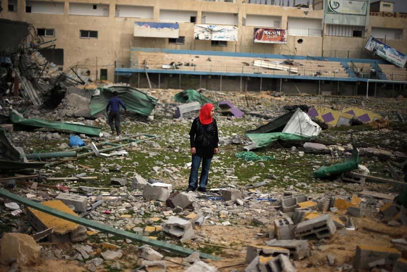 Seorang wanita Palestina menyaksikan reruntuhan stadion sepak bola, yang hancur akibat serangan udara Israel selama konflik delapan hari di Kota Gaza,Selasa (4/12). (Reuters/Suhaib Salem)