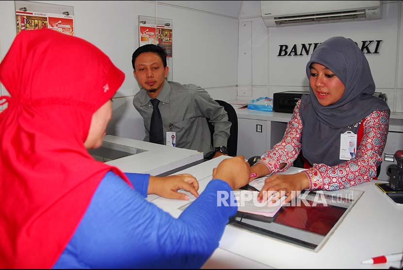 ugas Bank DKI (melayani nasabah dan wajib pajak di dalam mobile branch (kantor cabang berjalan), di Rusun Jatinegara Barat di Jakarta, Senin (4/9). Per Agustus 2017, Bank DKI telah melayani 453 ribu transaksi senilai Rp3,7 triliun untuk pembayaran PBB secara jemput bola  menggunakan mobile branch.