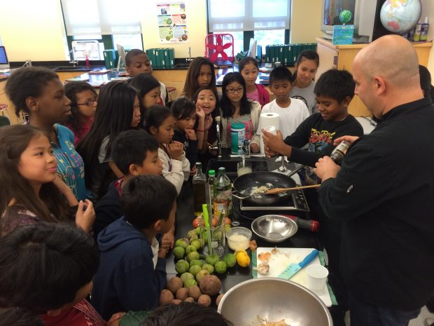 Children in a classroom gather around a chef and observe him preparing a dish for them to sample.