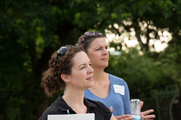 Two women listen during a farming workshop.