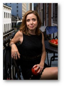 Photo of Danielle Nierenberg sitting on a balcony holding an apple.
