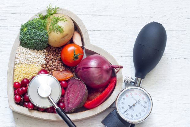 A heart-shaped bowl of vegetables and grains with a stethescope and blood pressure pump represent food as medicine.