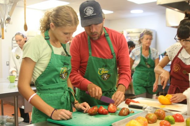 A teen chef learns how to cut tomatoes from a Ceres mentor.