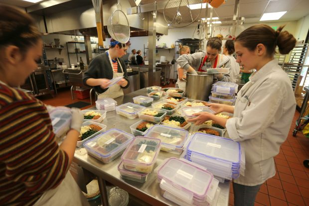 Teen chefs fill meal containers for the day's deliveries of nutritious food.