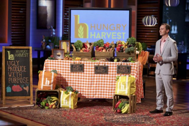 Standing next to a table laden with ugly produce, Evan Lutz gives his pitch on the TV show Shark Tank.
