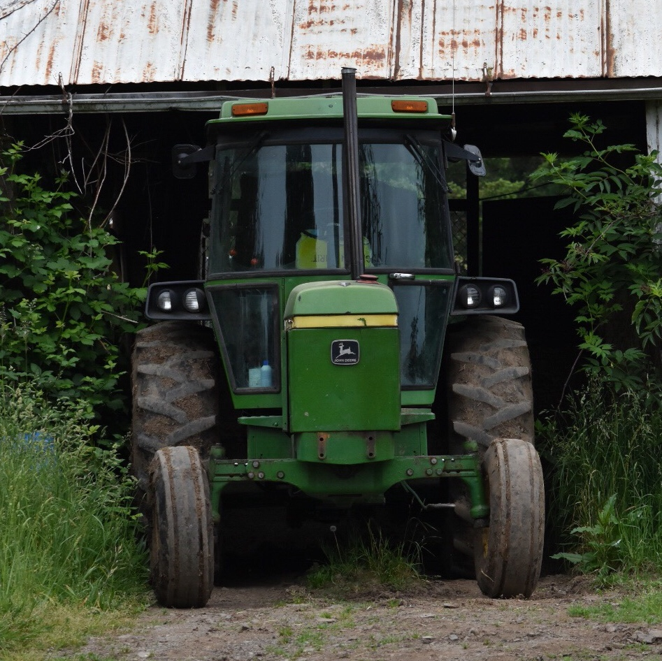A green tractor parked in a barn.