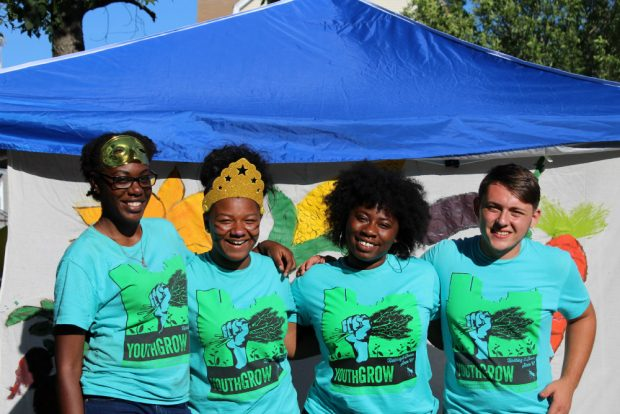 Four youth in matching t shirts with their arms around each other and smiling at the camera. Two of them are wearing fun masks.