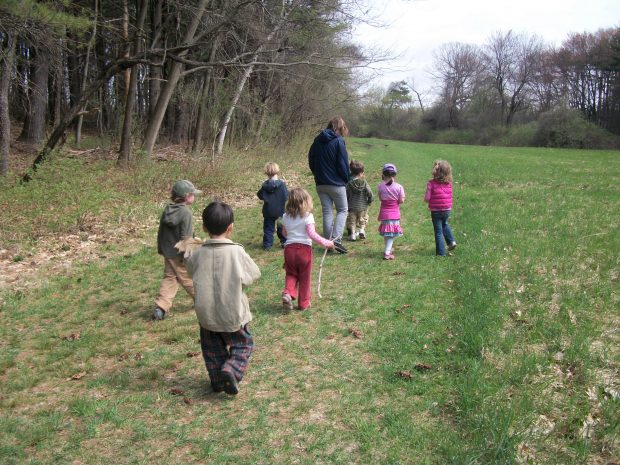 A group of small children and their teacher walk the paths at Drumlin Farm.