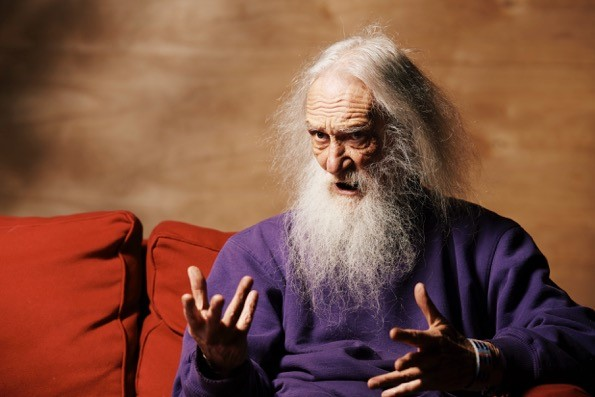 Jerome McGeorge has a craggy face and long white hair and beard and in this photo he talks with his hands during his interview.