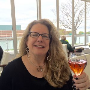 Diane Hatz smiles while holding up a glass of wine to cheers.