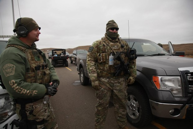 Two members of the Stutsman County SWAT team talk while deployed to watch protesters demonstrating against the Dakota Access Pipeline encroaching the water source near the Stand Rock Sioux Reservation, as they stand next to a police barricade on Highway 1806 in Cannon Ball, N.D., Sunday, Oct.