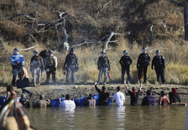 Dozens of protestors demonstrating against the expansion of the Dakota Access Pipeline wade in cold creek waters confronting local police, as remnants of pepper spray waft over the crowd near Cannon Ball, N.D., Wednesday, Nov.