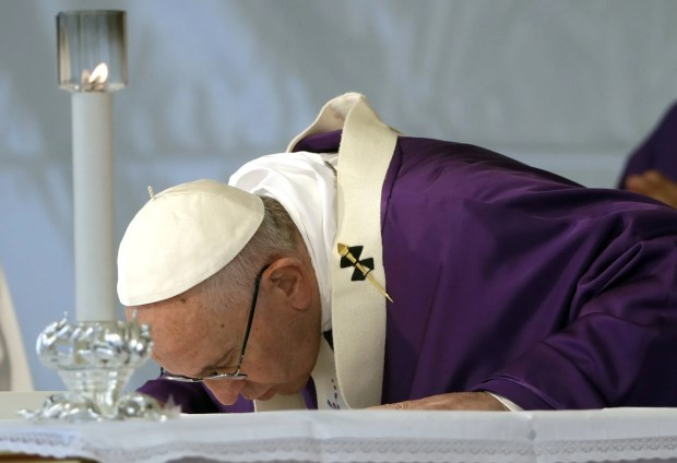 Pope Francis kisses the altar as he celebrates a Mass on the occasion of All Souls' Day, at the Prima Porta Cemetery in Rome, Wednesday, Nov.